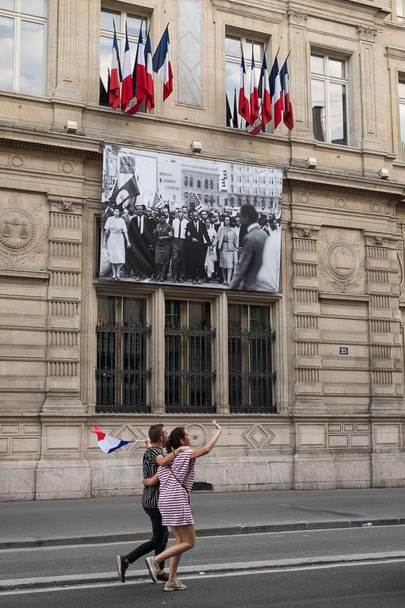 Des drapeaux, toujours de drapeaux. Passants fêtant la victoire de l'éqipe de France deavnt la photo de la marche de Martin Luther-King en Décembre 1964. La France championne du monde de Football - Paris Juillet 2018