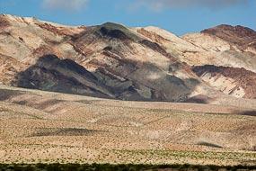 Dans la Vallée de la Mort, les pigments minéraux ont coloré ces dépôts volcaniques. Les sels de fer produisent les couleurs rouges, roses et jaunes. Le mica en se décomposant produit  la couleur verte. Le manganèse produit le violet.
