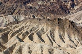 Zabriskie Point. Dans la Vallée de la Mort, les pigments minéraux ont coloré ces dépôts volcaniques. Les sels de fer produisent les couleurs rouges, roses et jaunes. Le mica en se décomposant produit  la couleur verte. Le manganèse produit le violet.