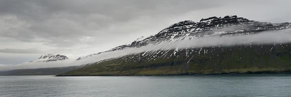 Arrivée dans le Seydisfjordur, les nuages flottent le long des falaises encore enneigées.