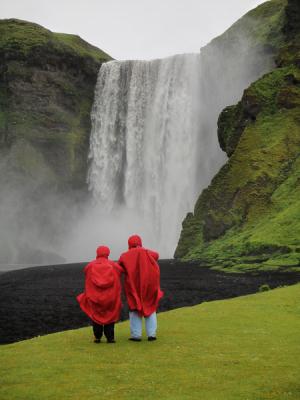 Touristes en tenue « climatique » devant la cascade de Skogarfoss, Islande