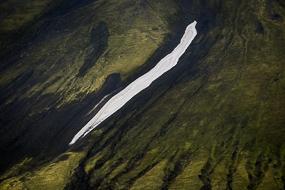 Coulée de neige sur un versant vert et noir dans la réserve de Fjallabak, Islande