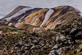 Blocs d'obsidienne devant les massifs ryolithiques du Landmannalaugar, Islande