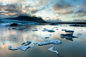 Reflets dorés du soleil couchant sur les morceaux de glace du lac Fjallsarlon, Islande