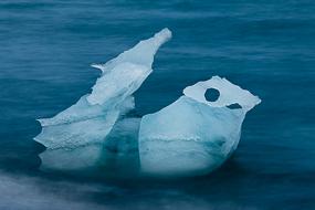 Les morceaux de glace sont charriés vers la mer depuis le lac de Jokulsarlon par un bras de rivière. Les vagues les érodent progressivement. Islande