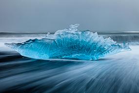 Iceberg errodé par les vagues sur la plage de sable noir à proximité de Jolulsarlon, Islande