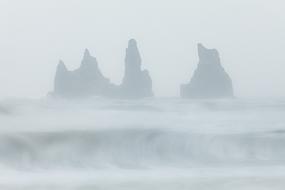 Vague et pitons basaltiques de Reynisdrangar dans le brouillard, Vik, Islande