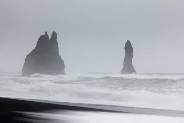 Les vagues entourent les stacks de Reynisdrangar à proximité de Vik, sud de l'Islande