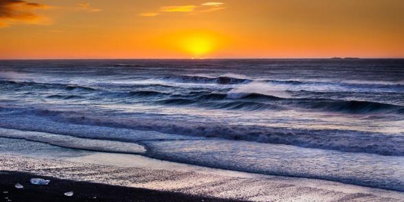 Lever de soleil sur la plage de sable noir devant la lagune glaciaire du Jokulsarlon, Islande