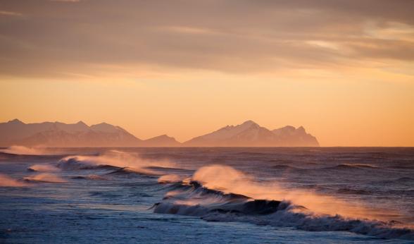Le lever du soleil éclaire l'écume des vagues qui déferlent sur la plage de sable noir de la lagune galcière du Jokulsarlon