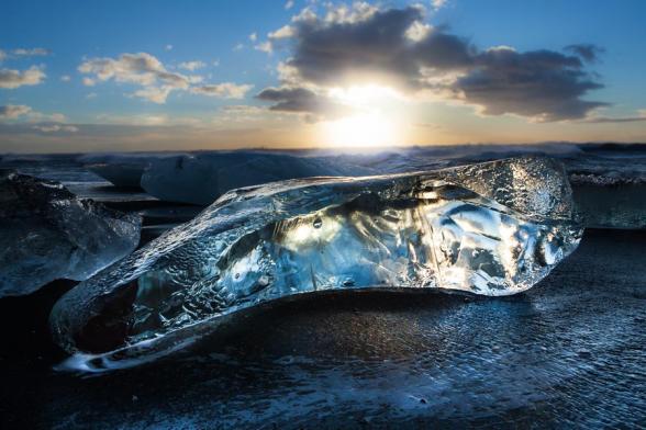 Le soleil levant révèle la transparence de ce gros glaçon, ancien iceberg, échoué sur la plage de sable noir de la lagune glaciaire de Jokulsarlon, Islande