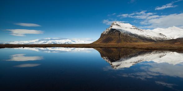 Symétrie du reflet d'une montagne dans une petite mare, à proximité du Jokulsalon, sud de l'Islande