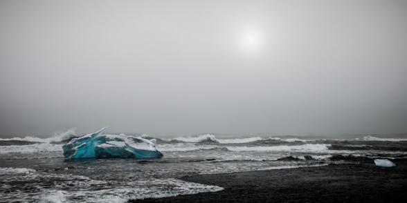 Iceberg échoué sur la plage de sable noir et battu par les vagues, en face de la lagune glaciaire du Jokulsarlon, Islande