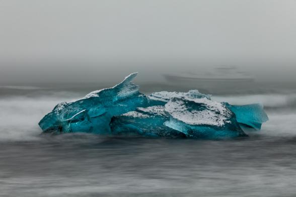 Le bateau fantôme. « A tribute to the Titanic ». Un bateau passe au large, dans le brouillard, pas très loin des icebergs échoués sur la plage en face du Jokulsarlon, Islande.