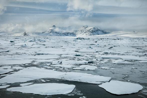 La neige recouvre les plaques de glace et les icebergs qui flottent sur la lagune glaciaire de Jokulsarlon, Islande