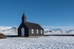 La petite église en bois de Budir au milieu du paysage enneigé de la péninsule de Snæfellsnes