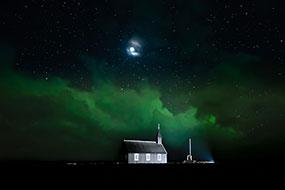 L'ovale auroral nimbe les nuages au dessus de l'église de Budir d'une couleur verte en ce soir d'éclipse lunaire, Islande