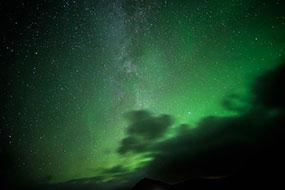 L'ovale auroral nimbe les nuages d'une couleur verte en ce soir d'éclipse lunaire, Islande