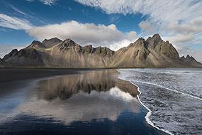 Les Vesturhorn se reflètent sur le sable noir mouillé de la plage, Islande