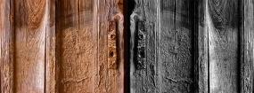 Malgré le vent, le sable reste accroché sur une vielle porte en bois