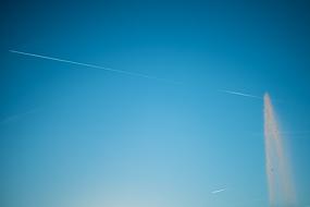 Jet d'eau et traces d'avions dans le ciel bleu parisien.